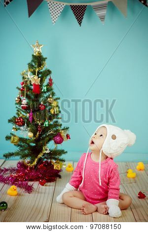 Baby Wearing White Knitted Beanie In Front Of Blue Background And Decorating Christmas Tree On Green