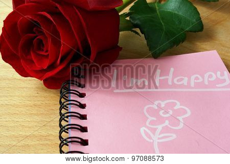 Pink notepad with I am happy and rose.