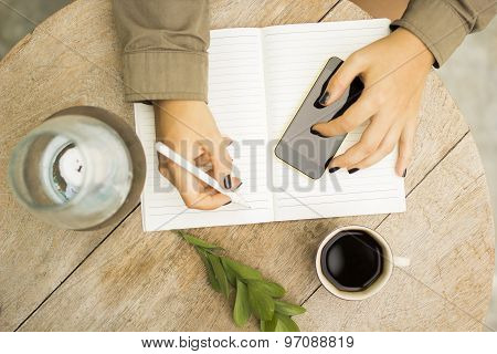 Woman Writes In Notebook With Cell Phone And Cup Of Coffee