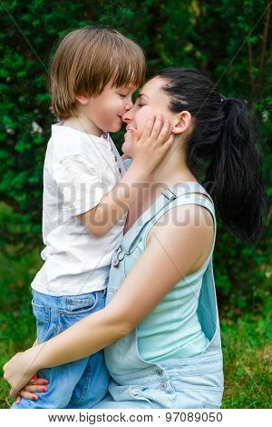 Loving son kissing his happy mother on the nose