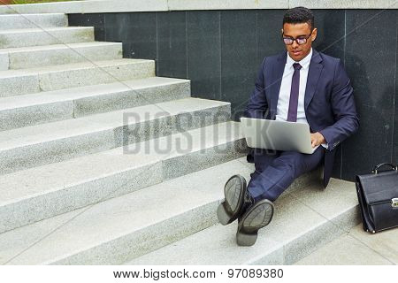 Young businessman using laptop in urban environment