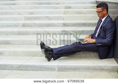 Young businessman using laptop while sitting on stairs