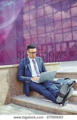 Young businessman sitting on stairs and typing