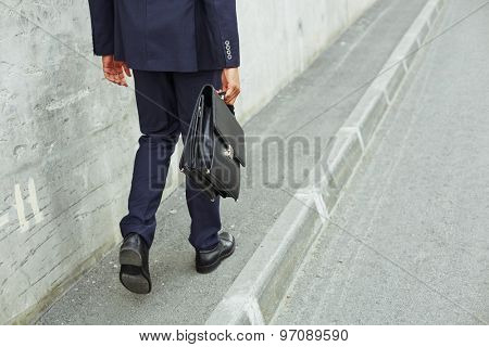 Rear view of businessman legs going to work