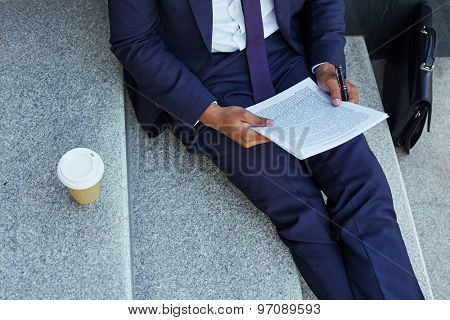 Close-up of businessman reading document on stairs