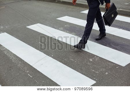 Elegant businessman with briefcase walking down crosswalk