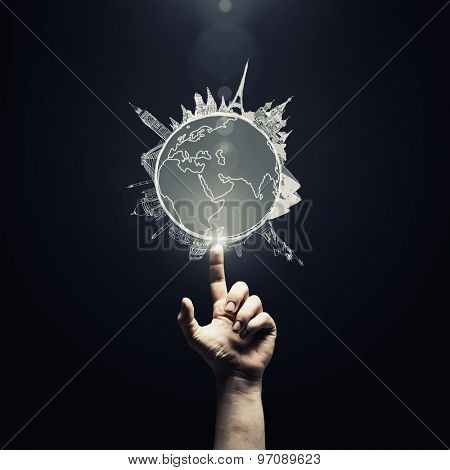 Human hand pointing with finger on Earth planet