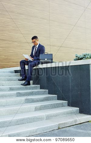 Confident businessman in suit working outside