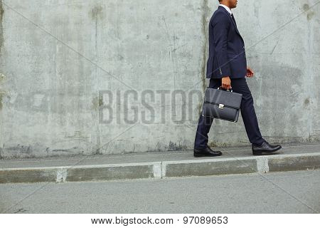 Modern businessman with briefcase walking along concrete wall