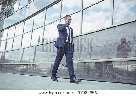 Young man in formalwear speaking on the phone while walking along modern building