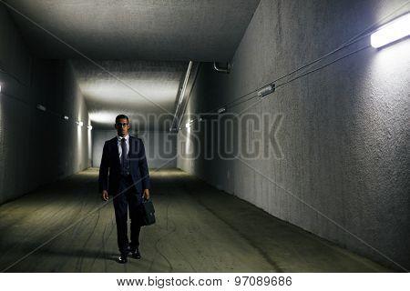 Elegant businessman with briefcase walking down tunnel
