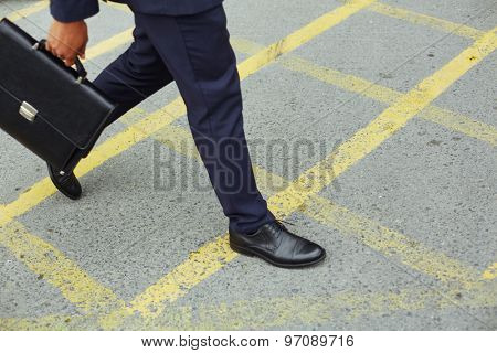 Legs of businessman with briefcase walking down trottoire