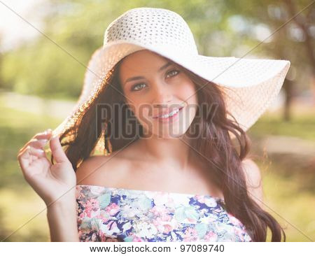 Pretty young woman in hat looking at camera in natural environment