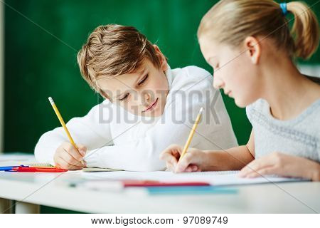 Youthful schoolkids drawing together at lesson