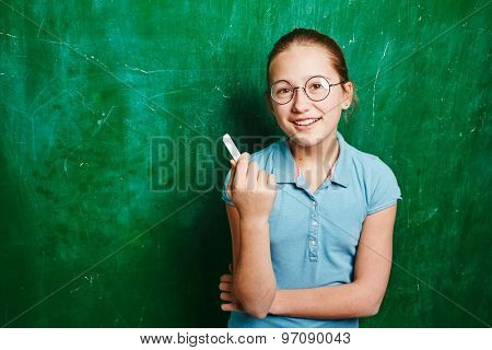 Successful schoolgirl with chalk looking at camera by blackboard
