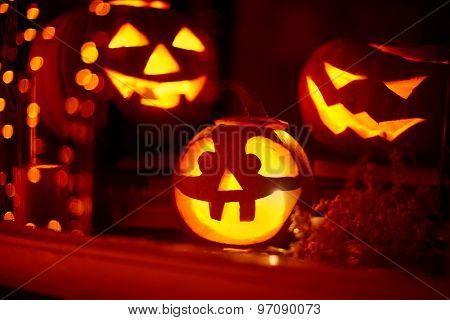 Eerie pumpkins burning in window on Halloween night