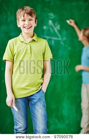 Cheerful schoolboy looking at camera on background of classmate by blackboard