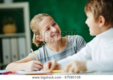 Happy schoolgirl looking at classmate while drawing