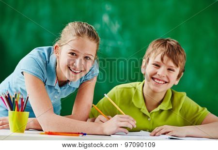Happy classmates drawing and looking at camera