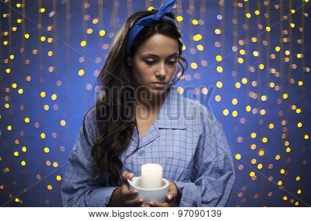 Young female in pyjamas holding candle on sparkling background