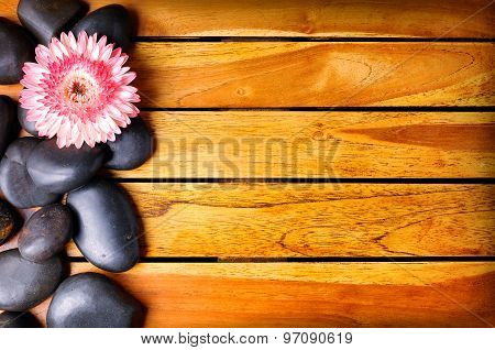 Black Stones And Flower On The Left Side On Wooden