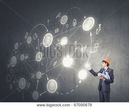 Young man engineer in helmet drawing connection lines