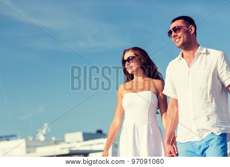 love, travel, tourism and people concept - smiling couple wearing sunglasses and walking in city
