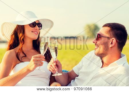 love, dating, people and holidays concept - smiling couple drinking champagne on picnic