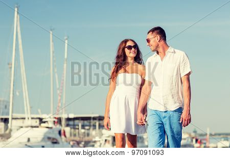 love, travel, tourism and people concept - smiling couple wearing sunglasses walking at harbor