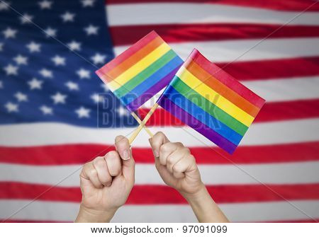 people, gay pride and homosexual concept - human hands holding rainbow flags over american flag background