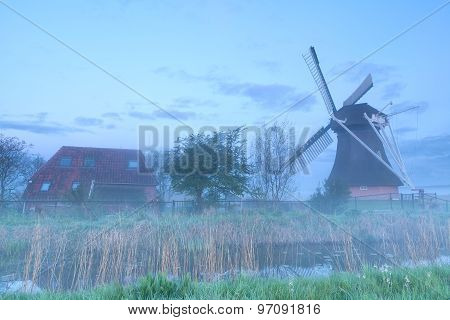 Windmill And Farmhouse In Fog