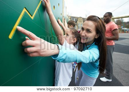 Girl On Climbing Wall In School Physical Education Class