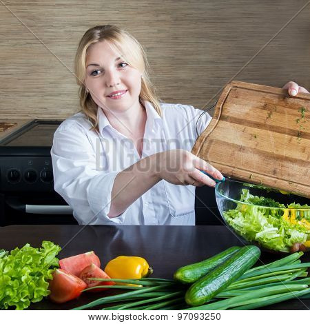 Young Woman Chops Vegetables In The Kitchen.