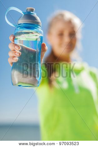 sport, fitness, exercise, nutrition and lifestyle concept - woman showing a bottle of water after doing sports outdoors