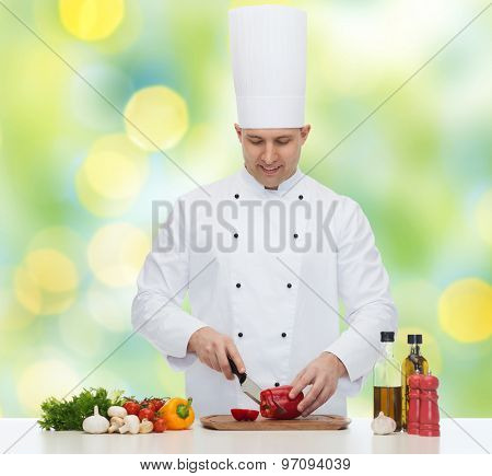 cooking, profession, vegetarian, food and people concept - happy male chef chopping pepper over green lights background