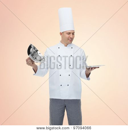 cooking, profession and people concept - happy male chef cook opening cloche cover over beige background
