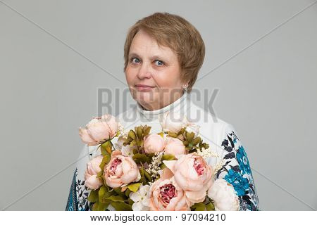 Old lady holding bouquet of flowers in hand