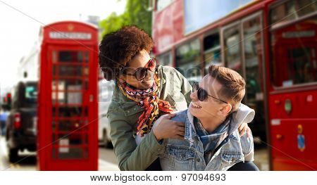 friendship, leisure, international, freedom and people concept - happy teenage couple in shades having fun over london city street background