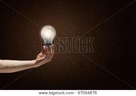 Human hand on dark background holding glass light bulb