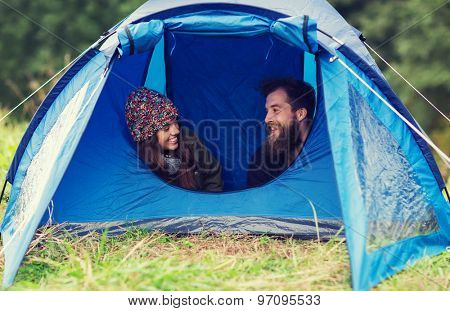 camping, travel, tourism, hike and people concept - smiling couple of tourists talking in tent