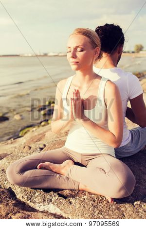 fitness, sport, friendship and lifestyle concept - smiling couple making yoga exercises sitting outdoors