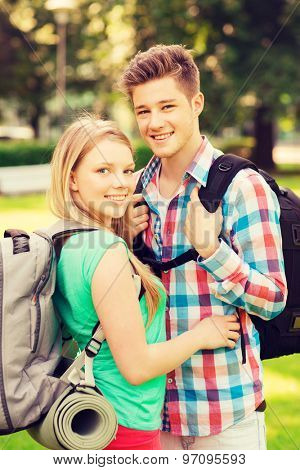 travel, vacation, tourism and friendship concept - smiling couple with backpacks in nature