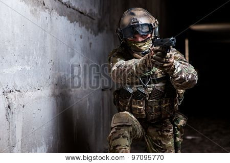 Armed Ranger In Camouflage Aiming His Gun In The Dark Room