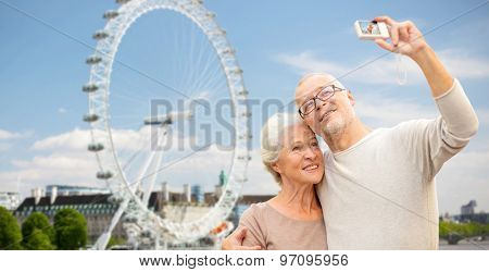 age, tourism, travel, technology and people concept - senior couple with camera taking selfie over london ferry wheel background