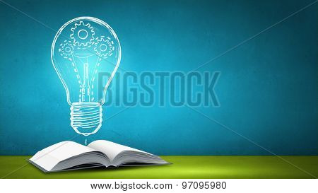 Old opened book and glowing light bulb