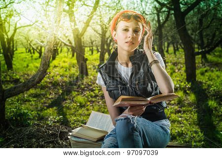Woman in park outdoor with tablet and book deciding what to use