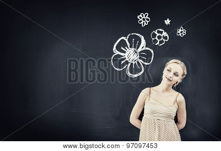Young pretty blond woman teacher near blackboard