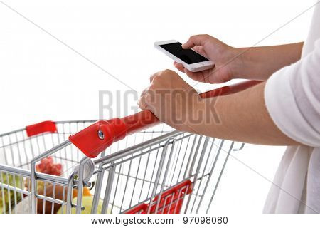 Young woman holding mobile phone and shopping cart isolated on white