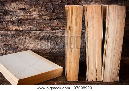 Old Books Standing In A Row Next To The Book On A Wooden Table