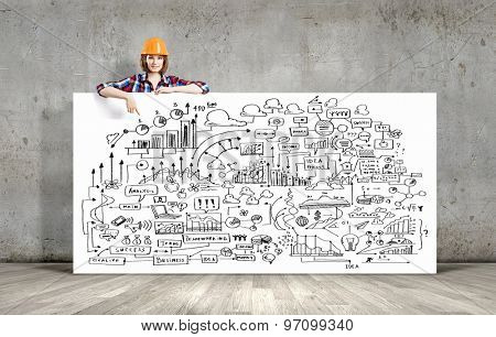 Young woman builder wearing helmet and holding banner with business sketches